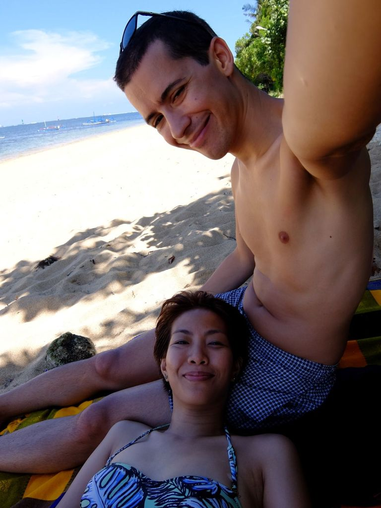 a woman lying on a man's lap by the beach