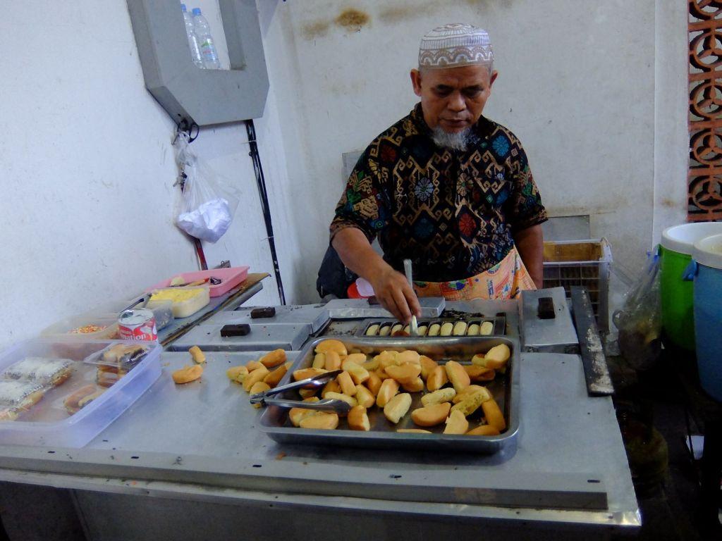 Man selling pancakes in Indonesian market