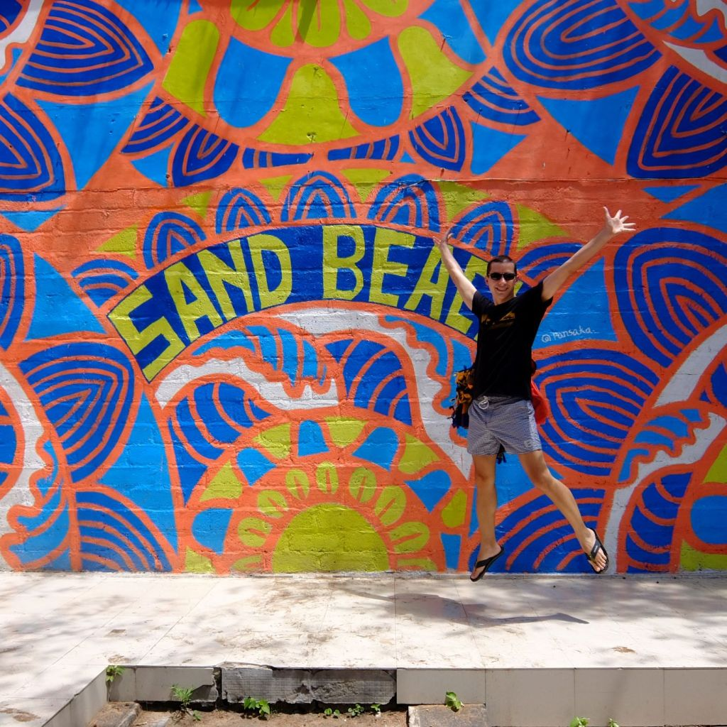 boy jumping in front of sand beach mural