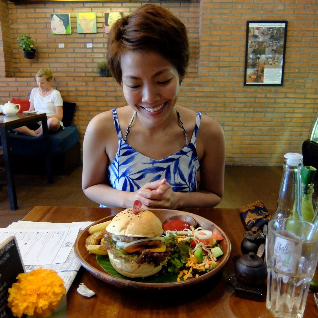 girl smiling at burger in front of her