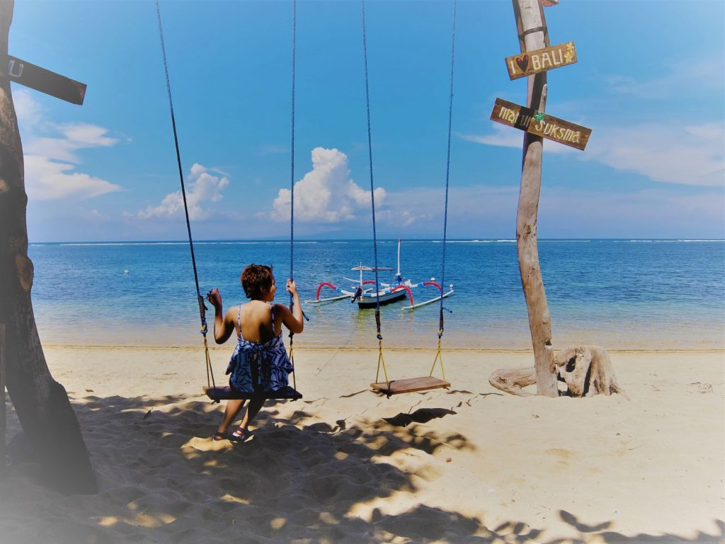 Girl in a swing by the beach