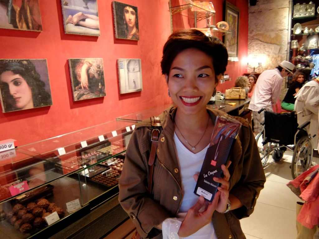 woman holding a bar of chocolate in a shop