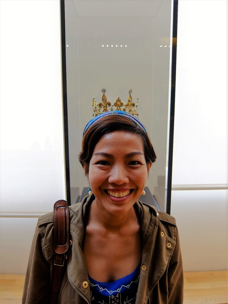woman standing in front of a crown in a museum