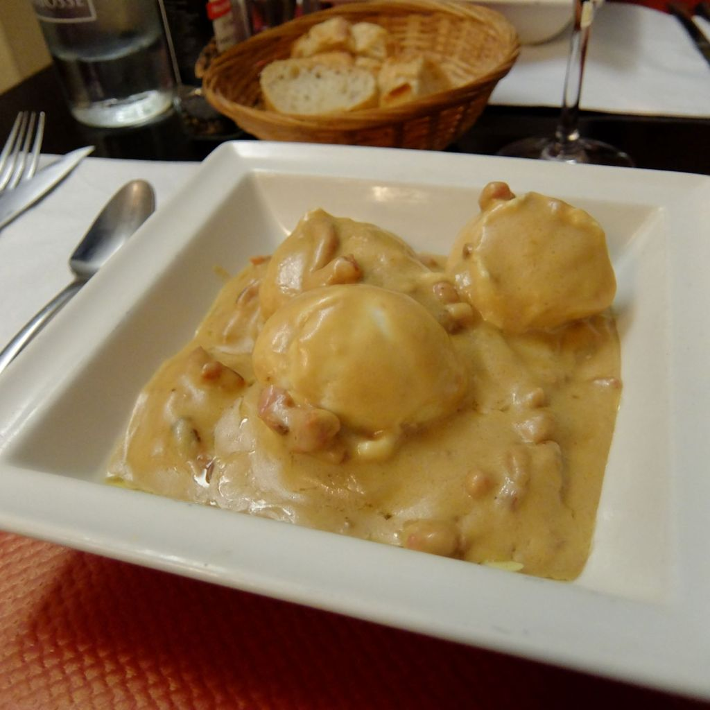 Plate of poached eggs in wine and cheese sauce